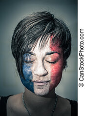 Woman with flag of France on face and closed eyes