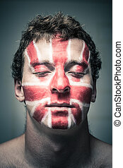 Man with British flag on face and closed eyes