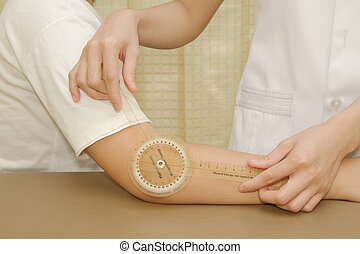 Physiotherapist measuring range of motion patients' elbow...