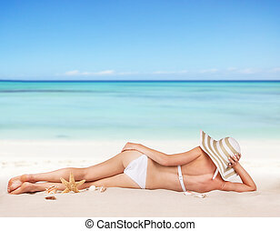Young woman relaxing on beach - Young blond woman relaxing...