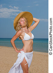 woman in white bikini and straw hat on the beach