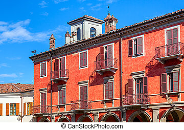 Red two storey building in Alba, Italy. - Facade of red two...