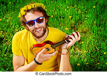 joyfulness - Happy carefree young man sitting on a grass and...