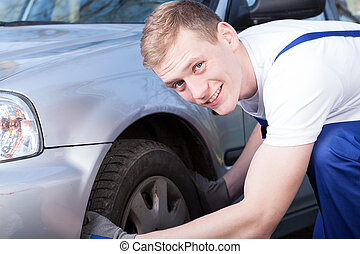 Auto mechanic checks a car tire - Smiling auto mechanic...