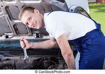 A mechanic repairing a car and smiling
