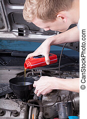 Mechanic completes the engine oil level - The mechanic...
