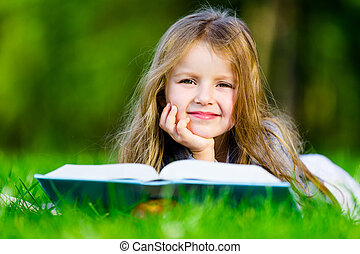 Girl reads interesting book on the grass - Girl reads...