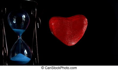 hourglass next to the dying red heart