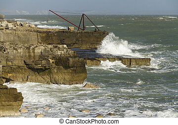 Crashing waves, rocks and a boat crane, Portland Bill -...
