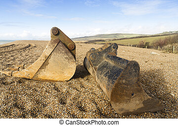 Digger scoops left on pebbled beach - Pebbled beach with two...
