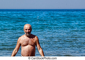 Bald man with a beard emerging from the sea in a spray