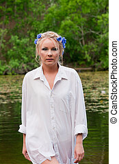 Beautiful woman in white coming out from pond
