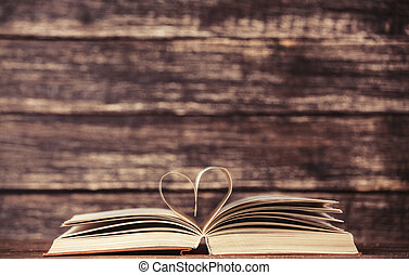 Vintage old books with heart shape on wooden table