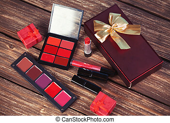 Cosmetics and gift box on woodent table.