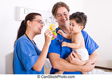Pediatrician and baby - Two pediatricians playing with...