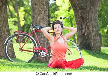 Happy girl in the park with bicycle on background.