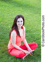 Brunettee girl with notebook on green grass in the park.