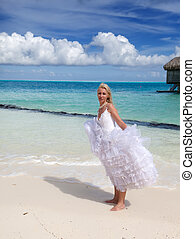 The young beautiful woman in a bride dress standing at sea edge