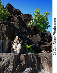 The woman in a long dress on black stones. Polynesia.