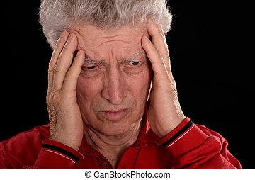 sad older man in red on a black background