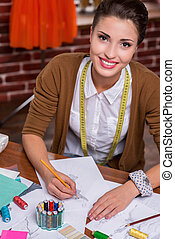 Beautiful fashion designer. Top view of beautiful young fashion designer drawing a fashion sketch and smiling at camera while sitting at her working place