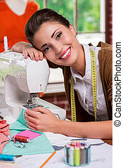 I love my job! Side view of beautiful female fashion designer leaning at the sewing machine and smiling while sitting at her working place