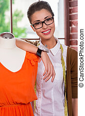 Successful fashion designer. Cheerful young female fashion designer leaning at the mannequin and smiling