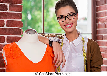 Beautiful and successful. Beautiful young female fashion designer leaning at the mannequin and smiling