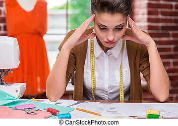 I need some fresh ideas. Tired young woman holding head in hands and looking at fashion sketches while sitting at her working place