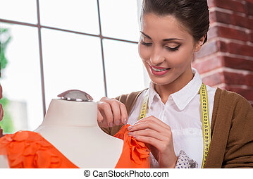 Confident tailor at work. Beautiful young fashion designer adjusting dress on the mannequin and smiling