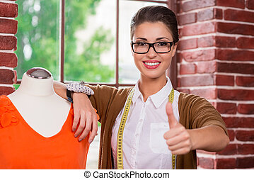 Young and successful fashion designer. Beautiful young female fashion designer leaning at the mannequin and showing her thumb up while standing in front of the window