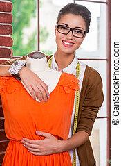 Beautiful fashion designer. Beautiful young female fashion designer embracing mannequin in orange dress and smiling