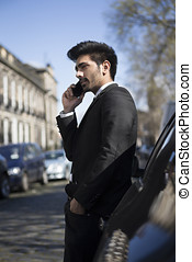 Indian businessman leaning against his car and talking on...