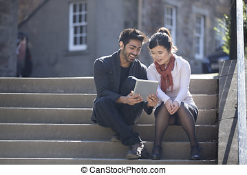 Asian friends sitting outdoors using digital Tablet. - Two...