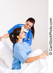 nurse and patient - friendly female nurse helping patient...
