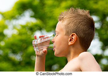 Boy drinking water - Young caucasian boy drinking from glass...