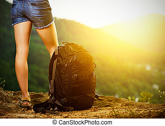 legs of a woman tourist and travel backpack on a mountain...