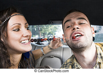 Young couple eating berries in the car