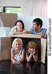 Happy family playing at home with boxes - Happy family...