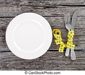 plate with a knife and fork wrapped in measuring tape on a...