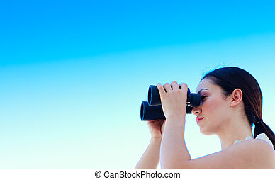 Businesswoman looking through binoculars with copy-space -...