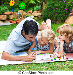 Smiling children drawing with their father in a park