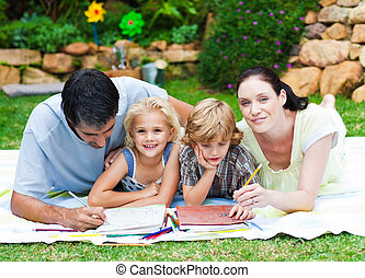 Happy family writing in a park - Happy family writing...
