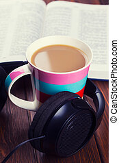 cup of coffee with headphones on wooden background