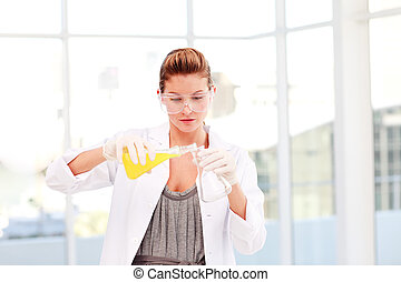 Blond female scientist examining a test-tube