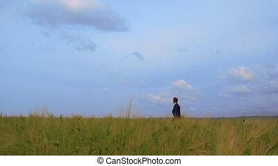 Business man walking through green field