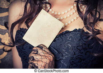 woman wearing black corset and pearls and holding a vintage...
