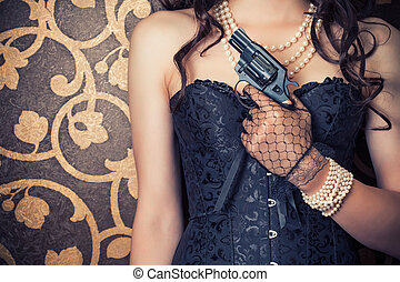 woman wearing black corset and pearls and holding a gun...