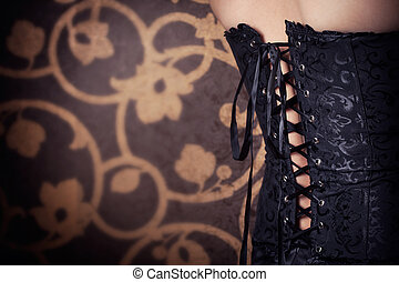woman wearing black corset and pearls against retro...