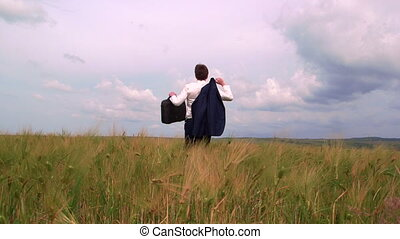 Business man with briefcase walking through green field